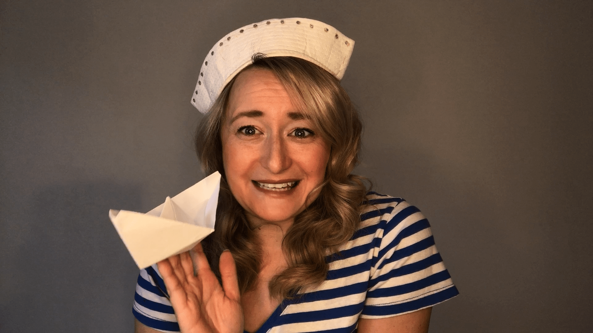 picture me dresses as a sailor, holding a paper boat